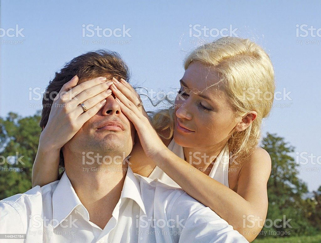 Young woman covering eyes of man royalty-free stock photo