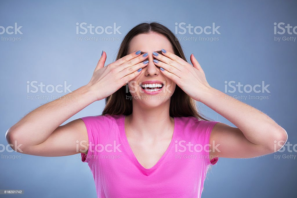Young woman covering eyes stock photo