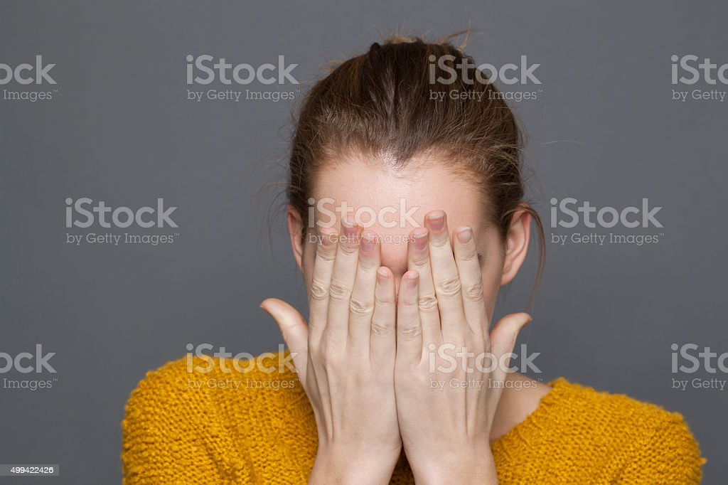 young woman covering eyes to express sadness,regret or blindness stock photo