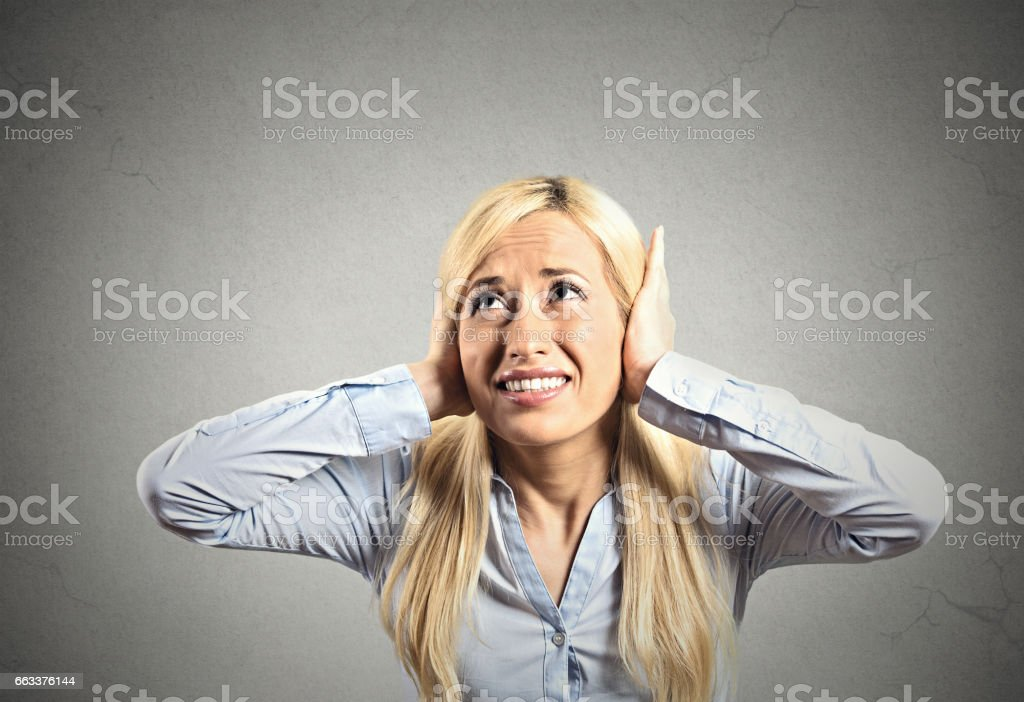 young woman covering her ears avoiding unpleasant rude situation stock photo