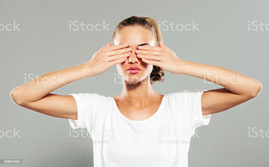 Young woman covering her eyes, Studio Portrait stock photo