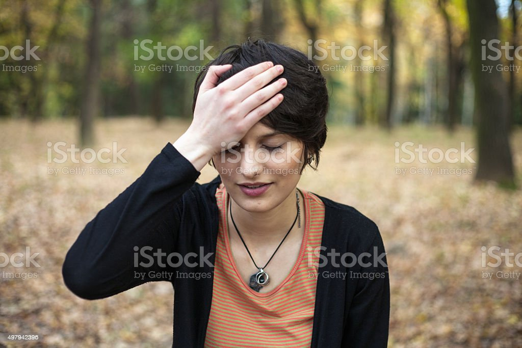 Young woman covering her forehead with palm stock photo