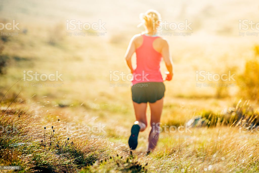 Young woman cross-country running stock photo