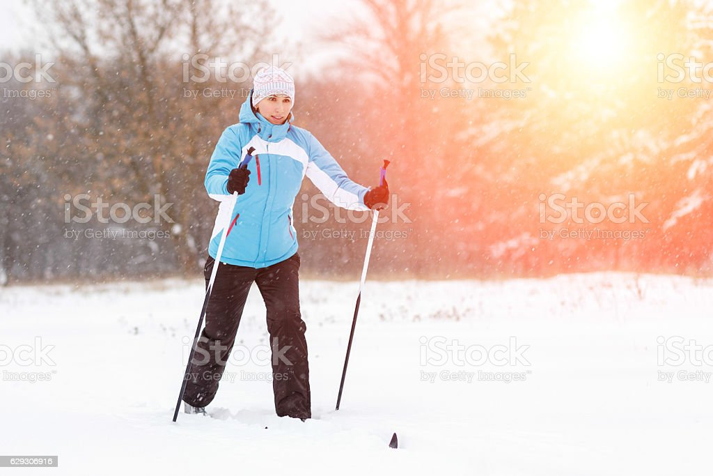 Young woman cross-country skiing in winter park stock photo