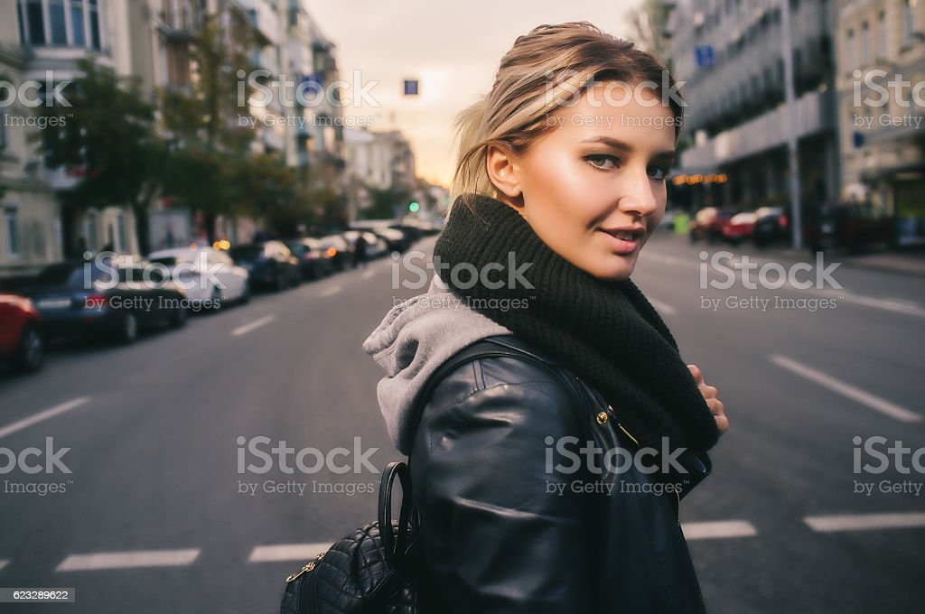 Young woman crossing the street in the city stock photo
