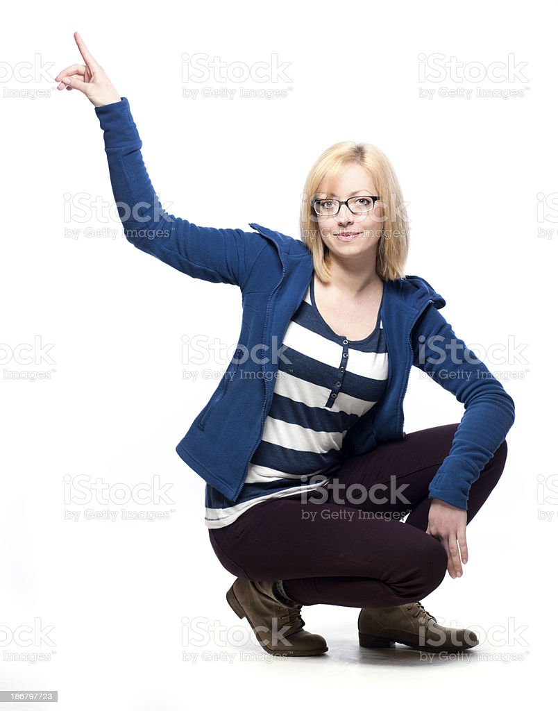Young woman crouching and pointing stock photo