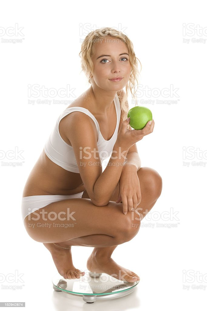 Young woman crouching on bathroom scale royalty-free stock photo