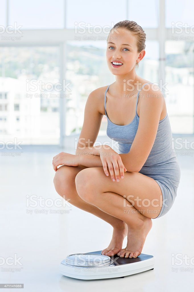Young woman crouching on weighing machine royalty-free stock photo