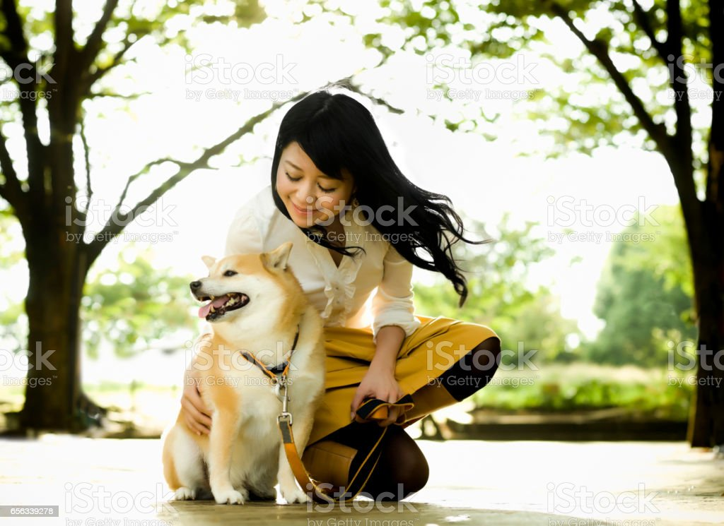 Young Woman Crouching to Pet a Dog stock photo