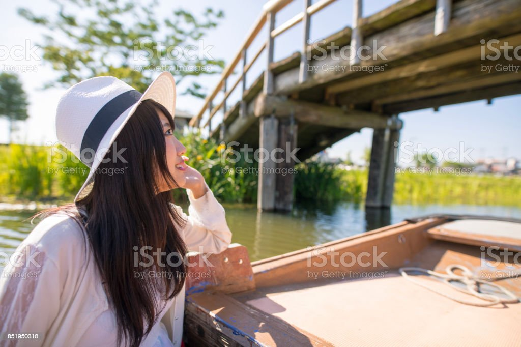 Young woman cruising with small sightseeing boat stock photo