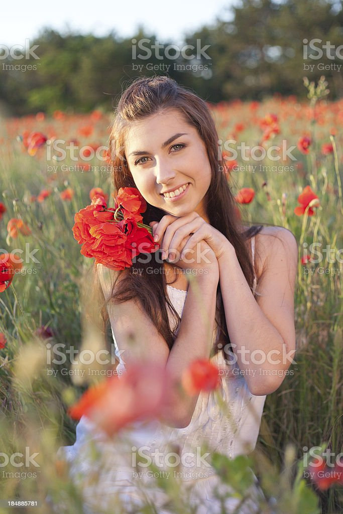 Young woman cuddling bouquet of red poppies, enjoying nature royalty-free stock photo