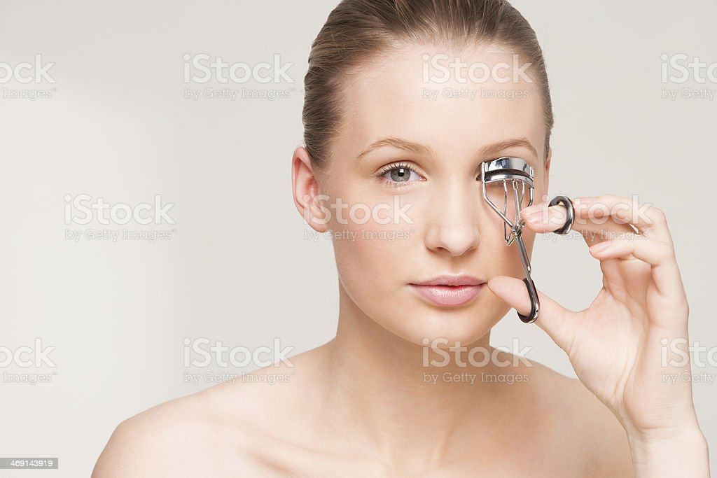 Young Woman Curling Her Eyelashes stock photo
