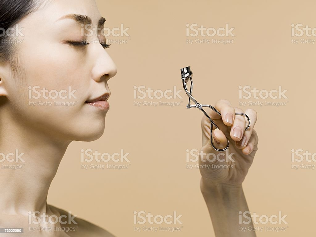 Young woman curling lashes stock photo