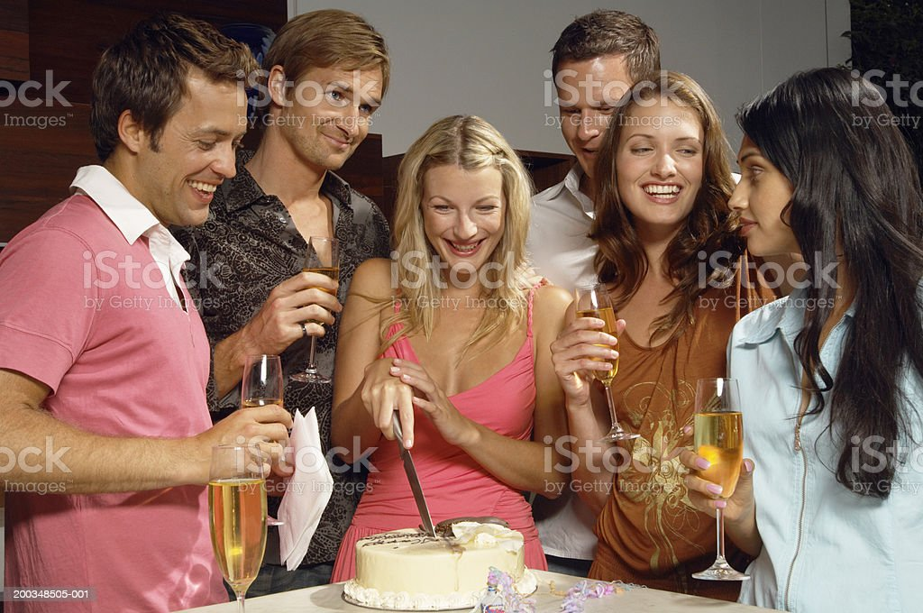 Young woman cutting birthday cake with friends holding champagne royalty-free stock photo