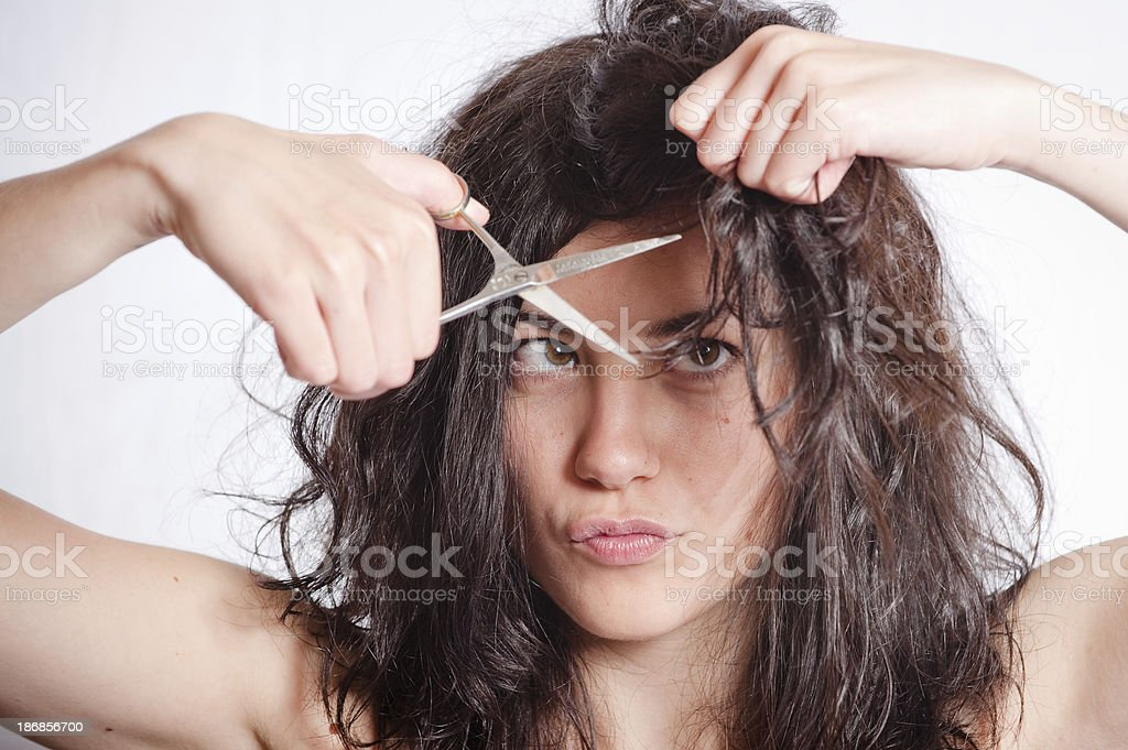 A young woman cutting her own hair stock photo
