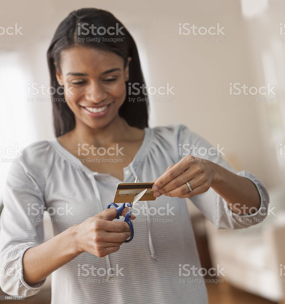 Young Woman Cutting up Credit Card Smiling stock photo