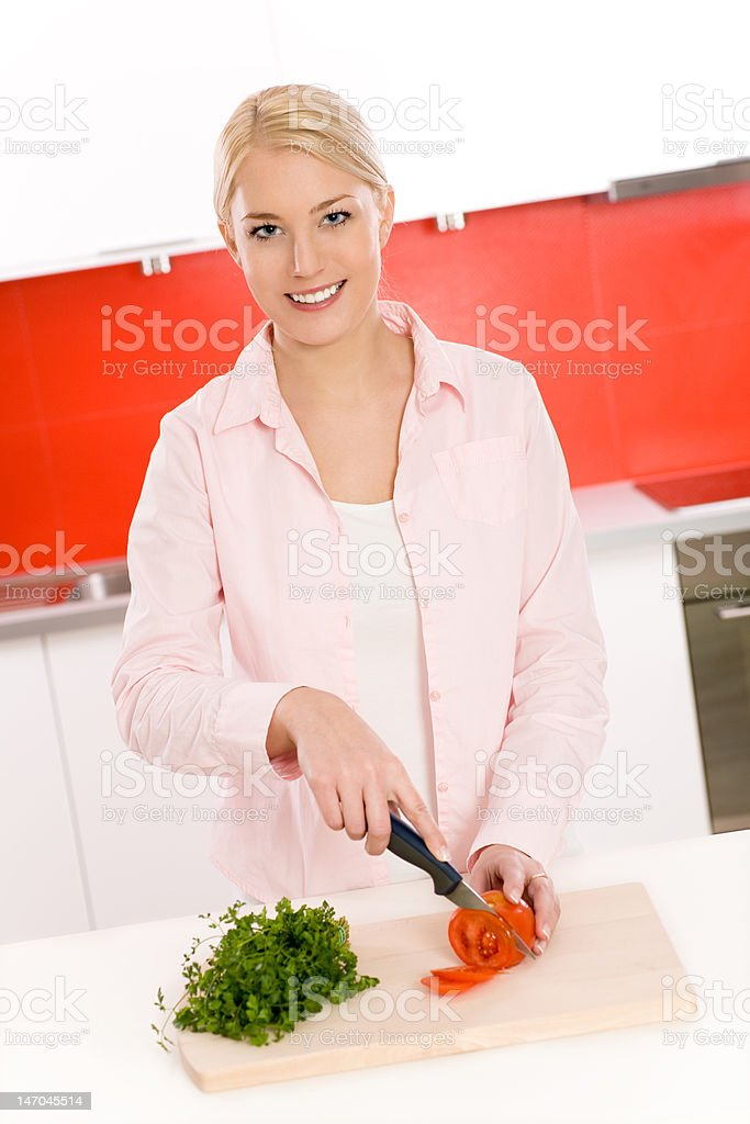 Young woman cutting vegetables in kitchen royalty-free stock photo