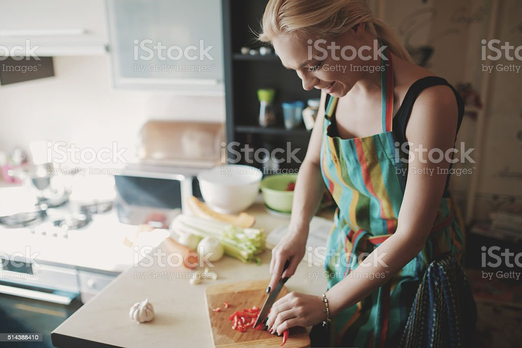 Young woman cutting vegetables stock photo