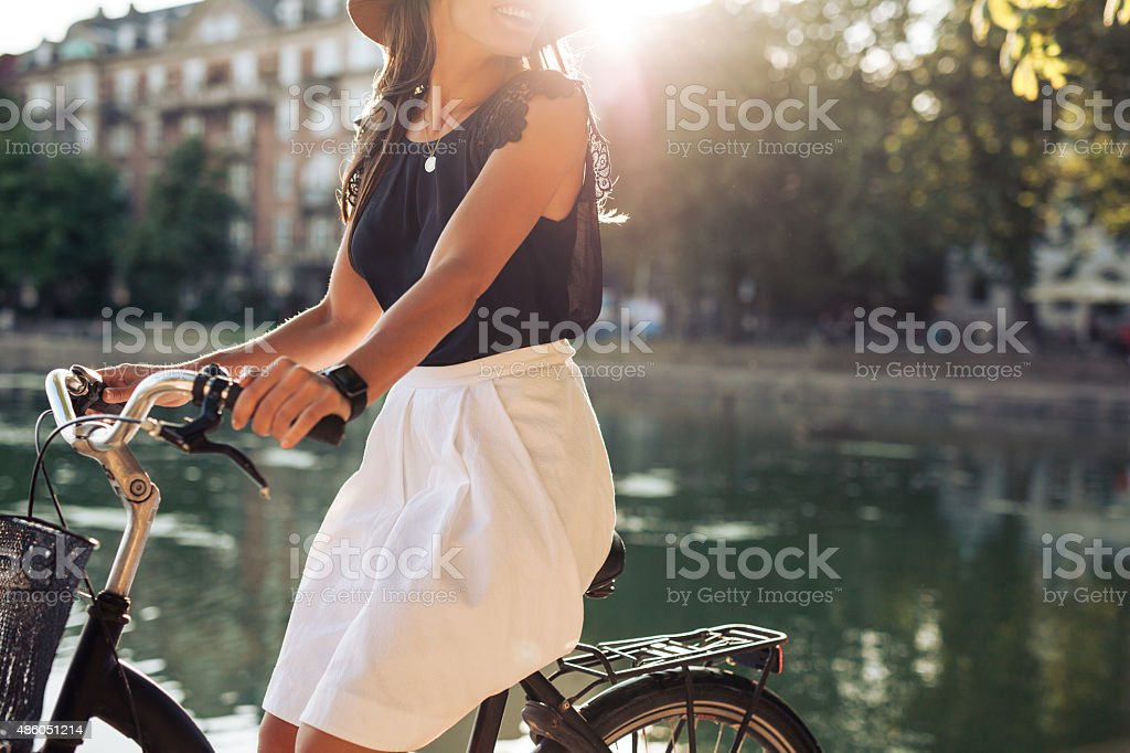 Young woman cycling by a pond stock photo
