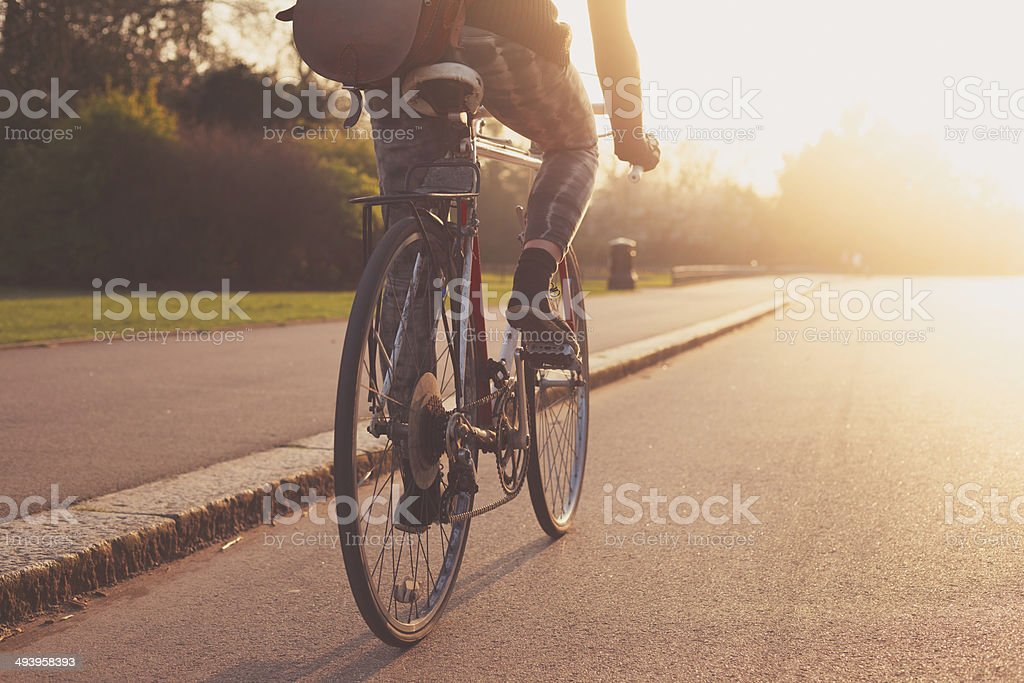 Young woman cycling in the park at sunset stock photo