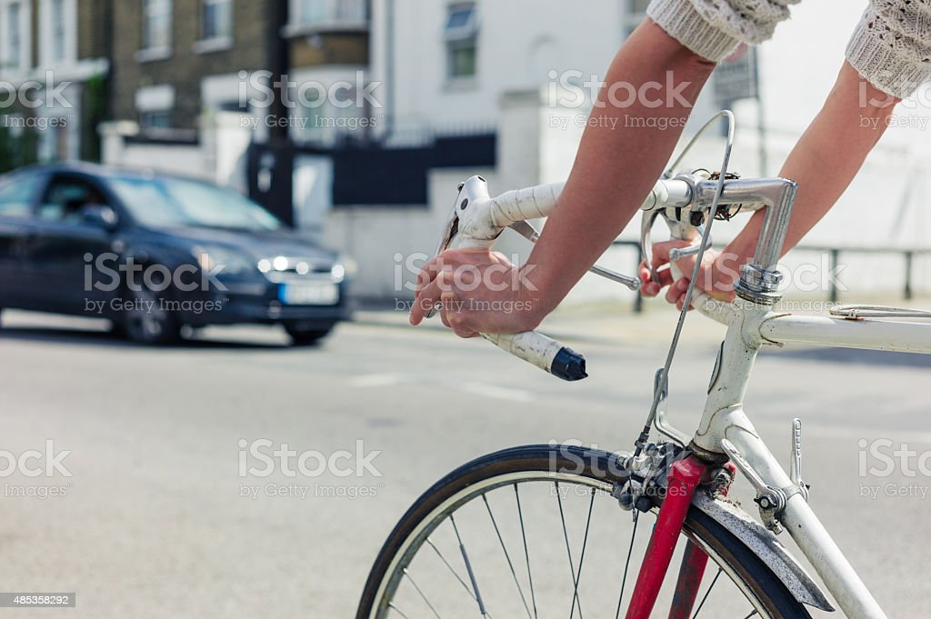 Young woman cycling on a road in the city stock photo