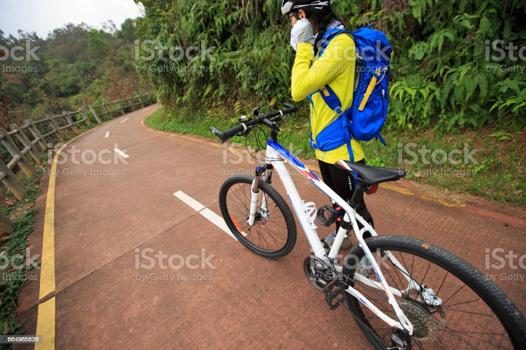young woman cyclist put on bike helmet before riding stock photo