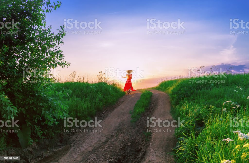 Young Woman Dancing Against The Setting Sun stock photo