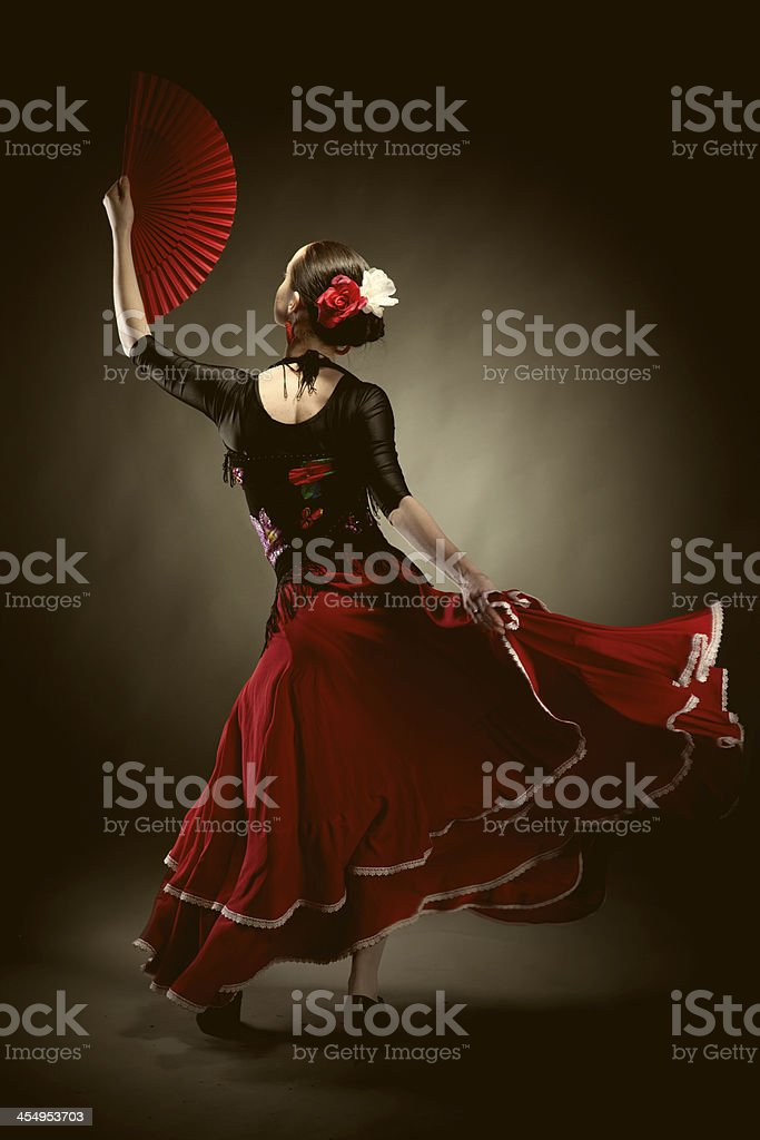 young woman dancing flamenco on black stock photo