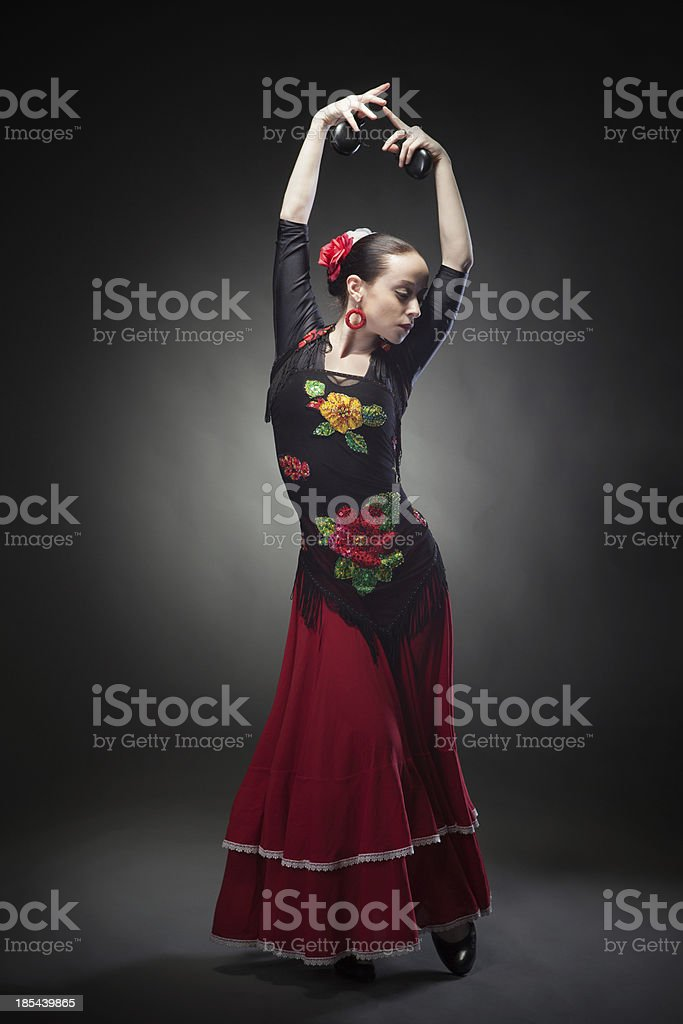 young woman dancing flamenco with castanets on black stock photo