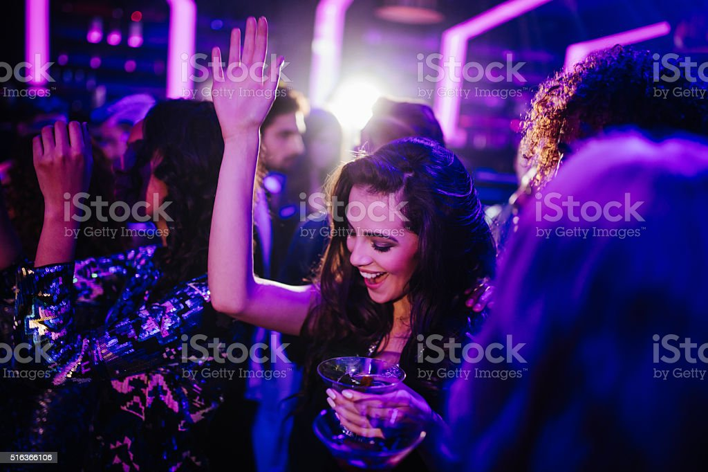 Young woman dancing in a club with a cocktail stock photo