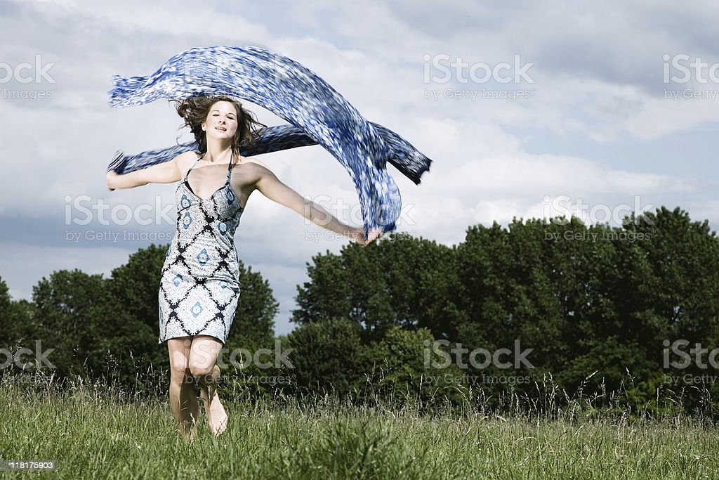 Young Woman Dancing In A Green Meadow stock photo