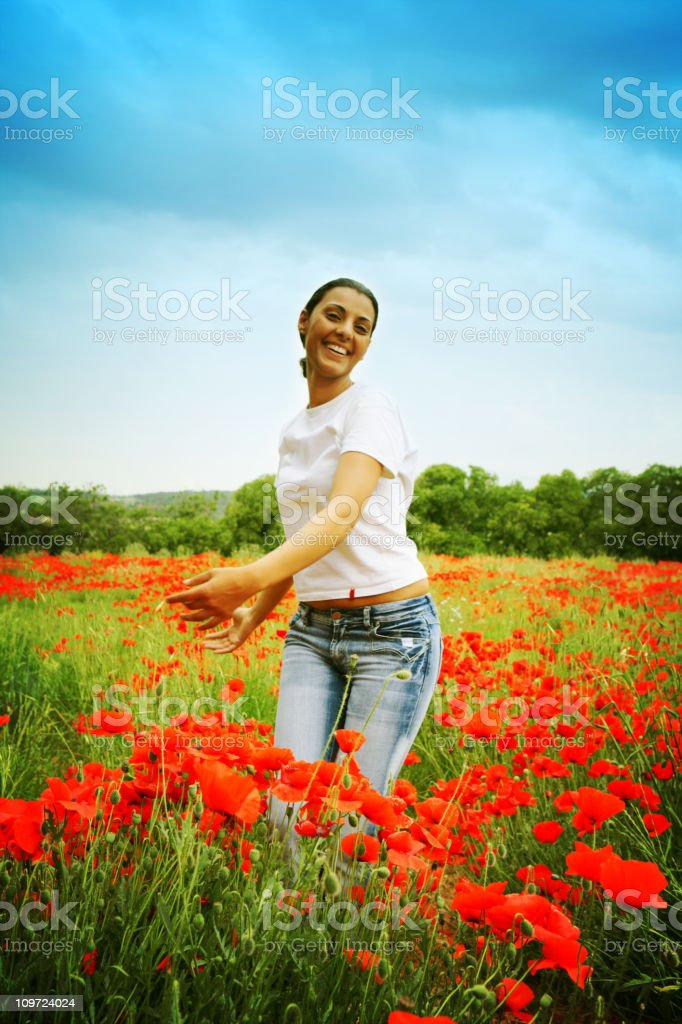 Young Woman Dancing in Field Full of Flowers royalty-free stock photo