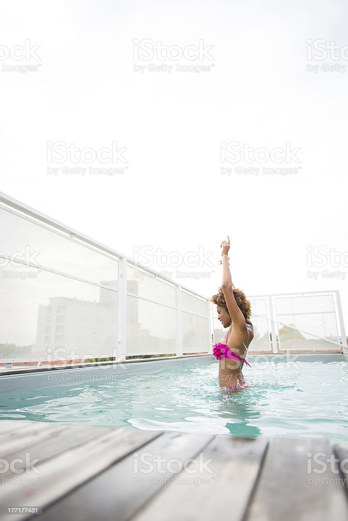 Young woman dancing in the swimming pool royalty-free stock photo
