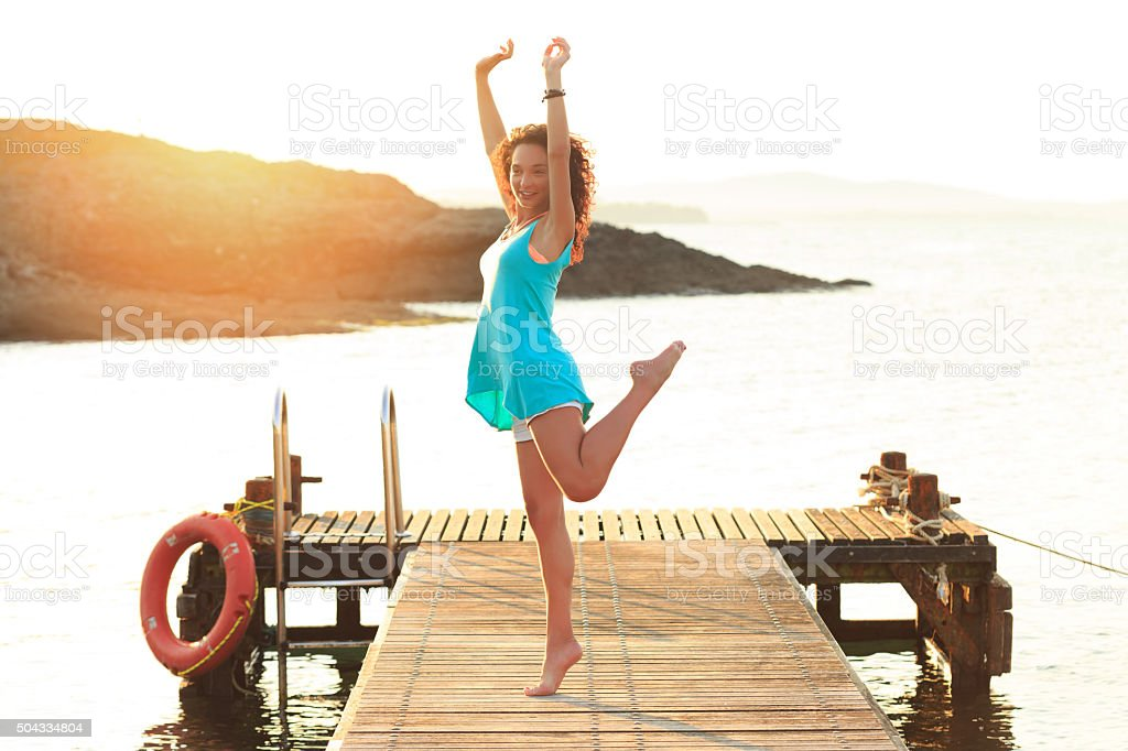 Young woman dancing on the pier stock photo