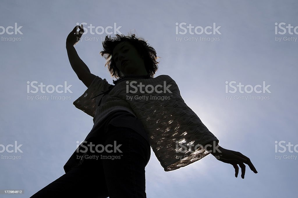 Young Woman Dancing Silhouetted by Sun, Blue Sky Clouds Background royalty-free stock photo
