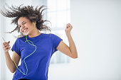 Young woman dancing to mp3 player.