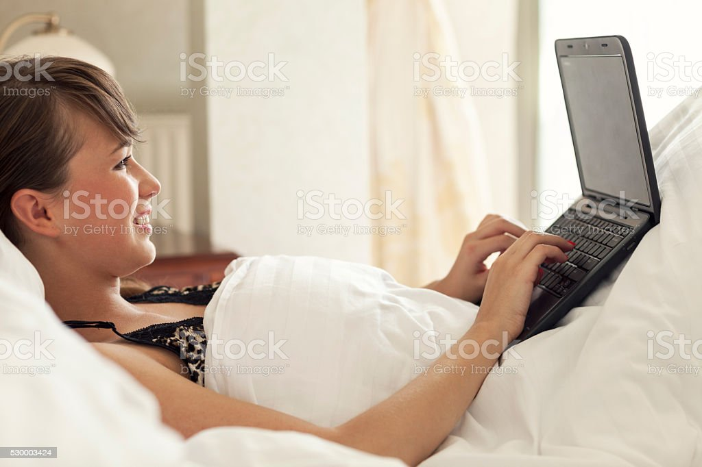 Young Woman Dating Online In Bed stock photo