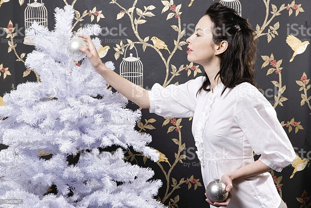 Young woman decorating christmas tree royalty-free stock photo