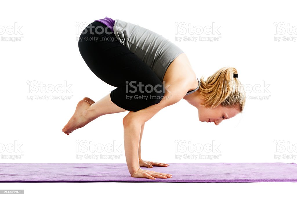 Young woman demonstrating Crow pose on a yoga mat stock photo