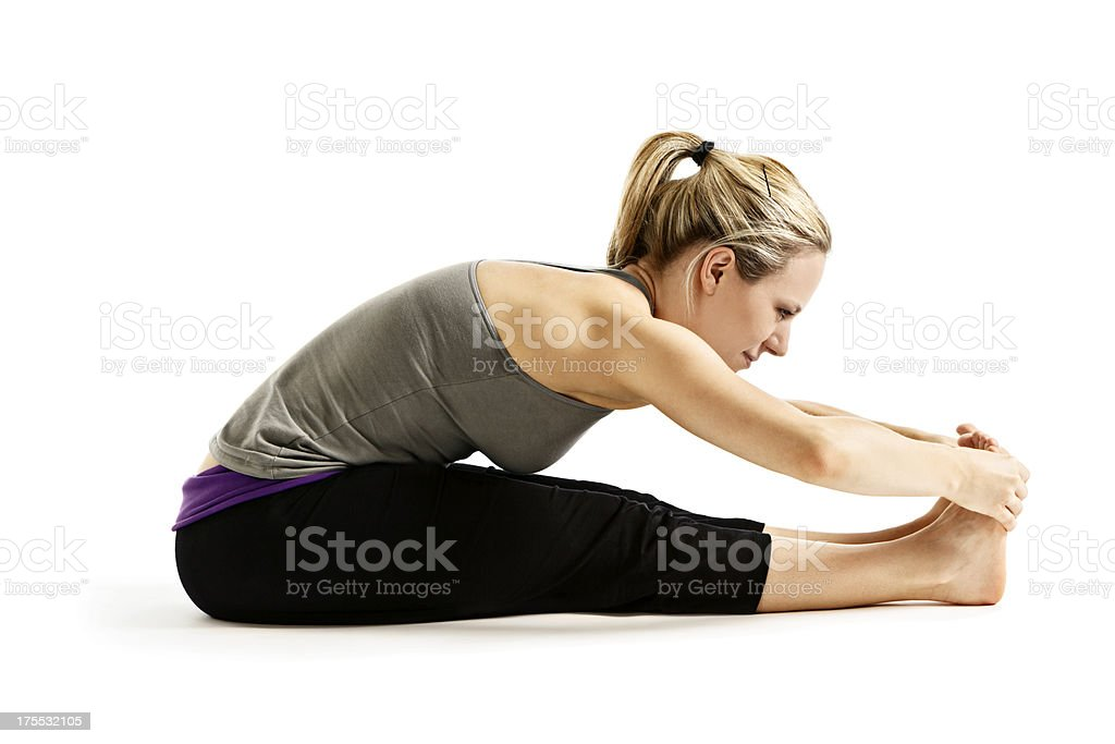 Young woman demonstrating Paschimottanasana or seated forward bend yoga posture stock photo