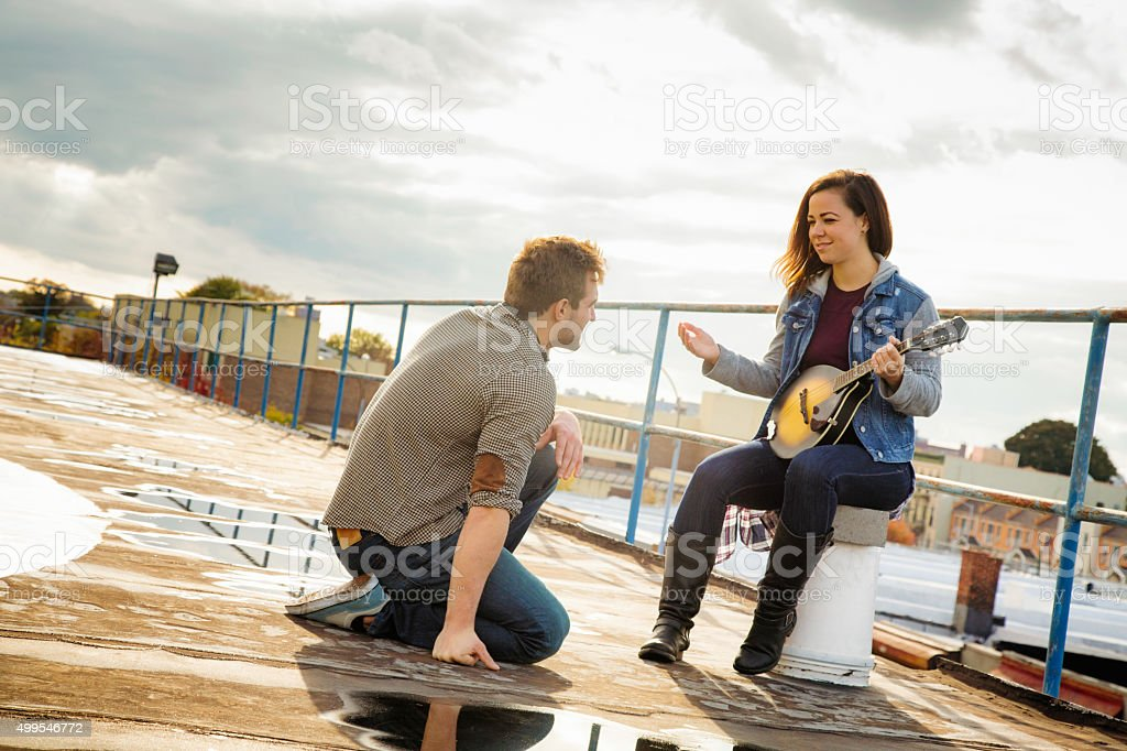 Young woman discussing performance while rehearsing on rooftop stock photo