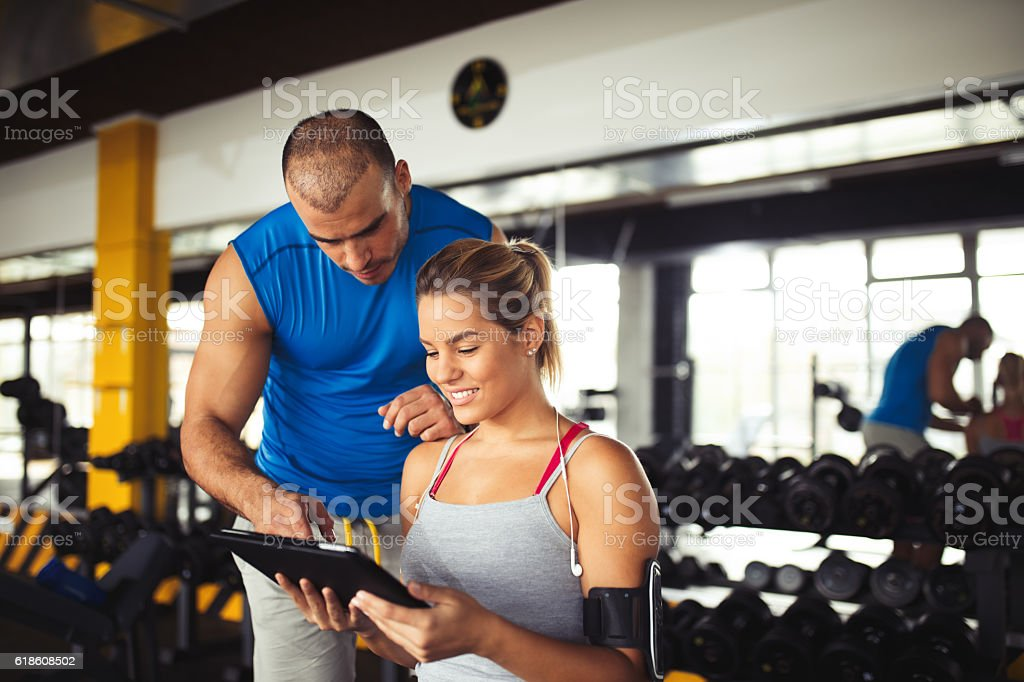 Young woman discussing workout plan with fitness instructor stock photo