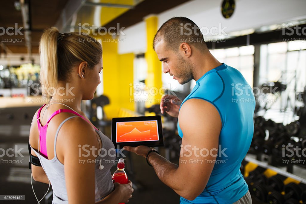 Young woman discussing workout progress with fitness instructor stock photo