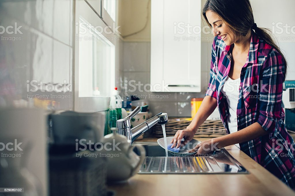 Young woman dish washing stock photo