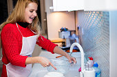 Young woman dish washing