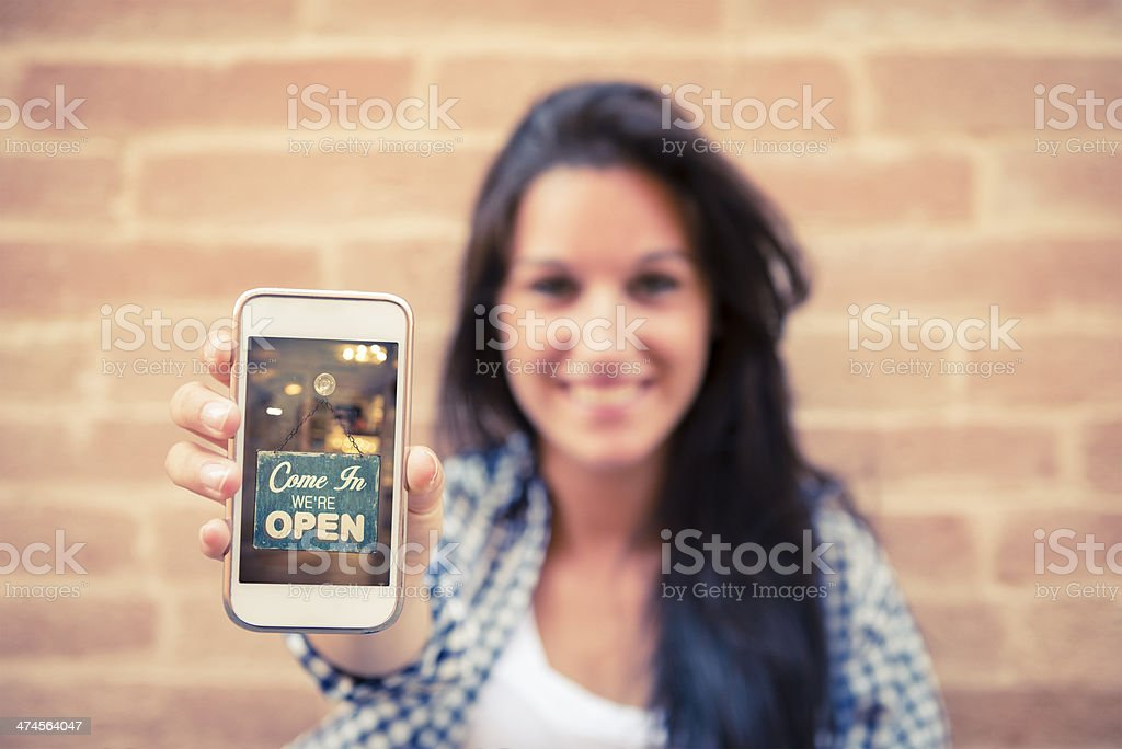 Young woman displays photo of open sign on phone stock photo