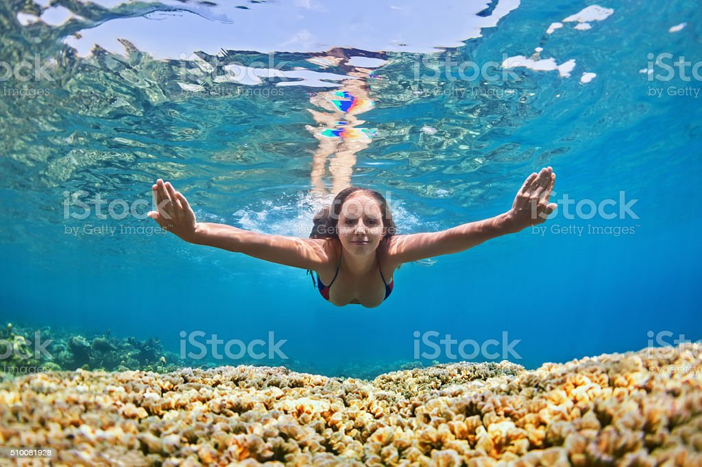 Young woman dive underwater over coral reef in sea stock photo