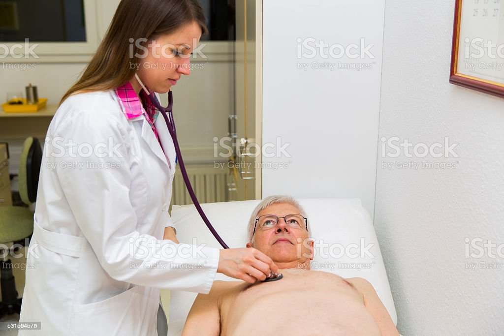 Young woman doctor checking patients heart with stethoscope stock photo