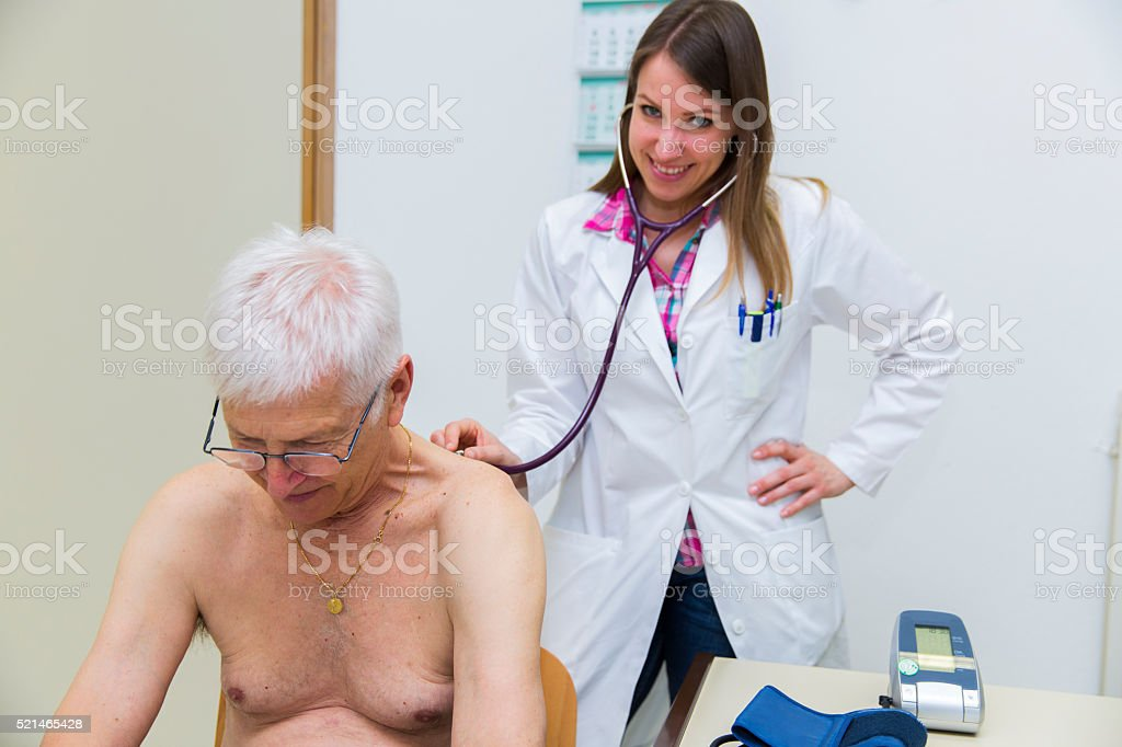 Young woman doctor checking patients lungs with stethoscope stock photo