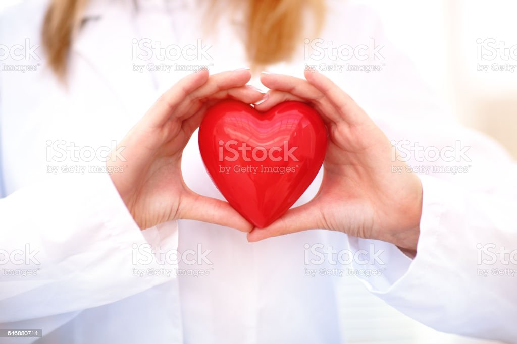 Young woman doctor holding a red heart, standing on gray background stock photo